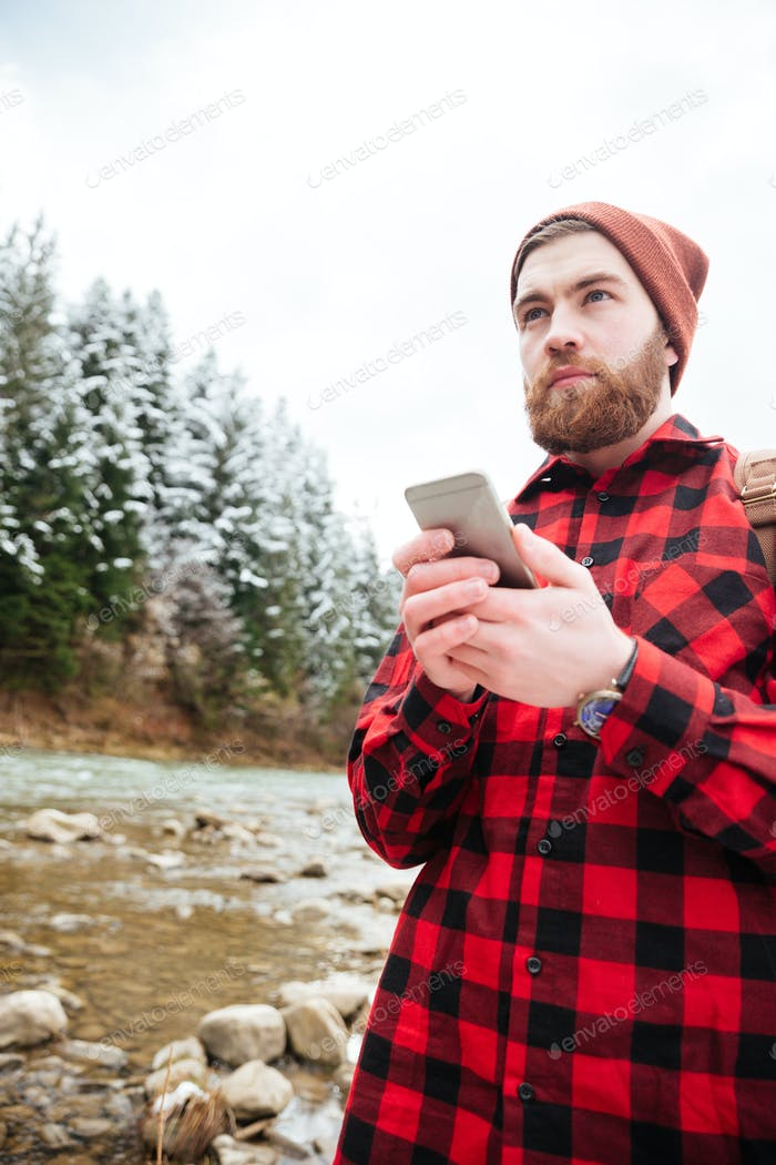 Handsome man using smartphone outdoors