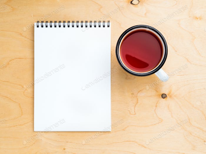 metal mug with tea, empty a blank sheet of notepad on the spiral on a beige wooden background
