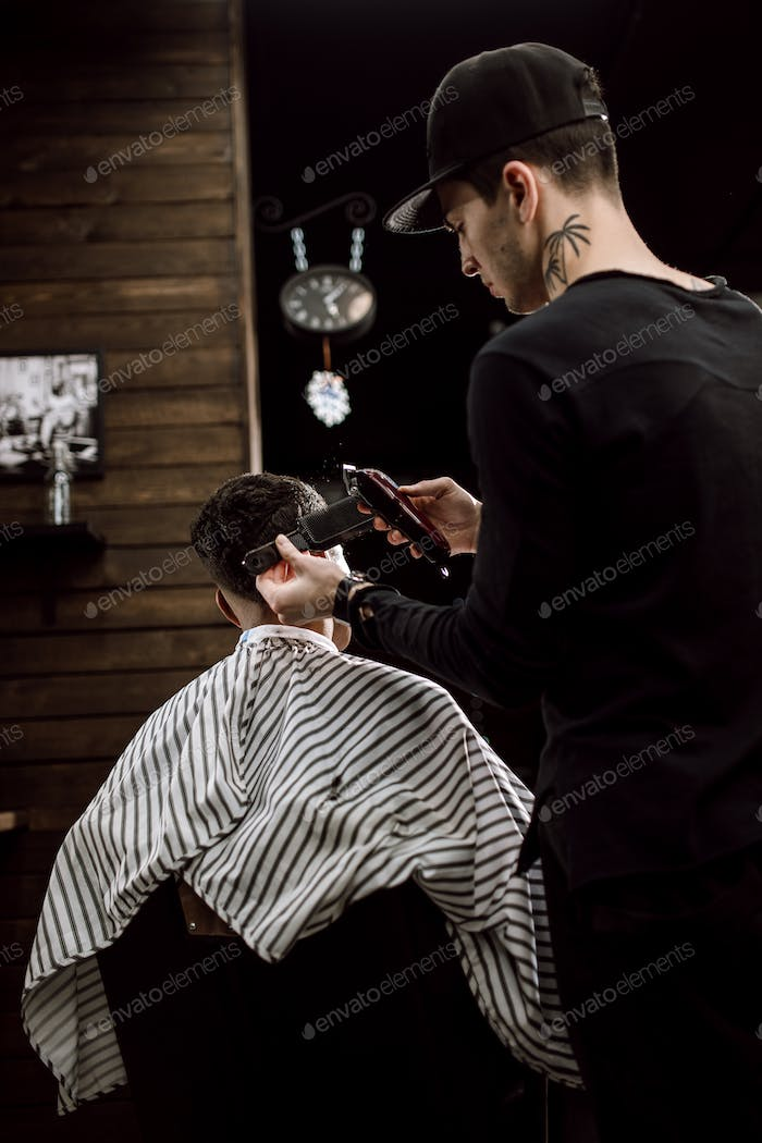 The fashion barber makes a razor cut hair for a stylish black-haired man in a stylish barbershop