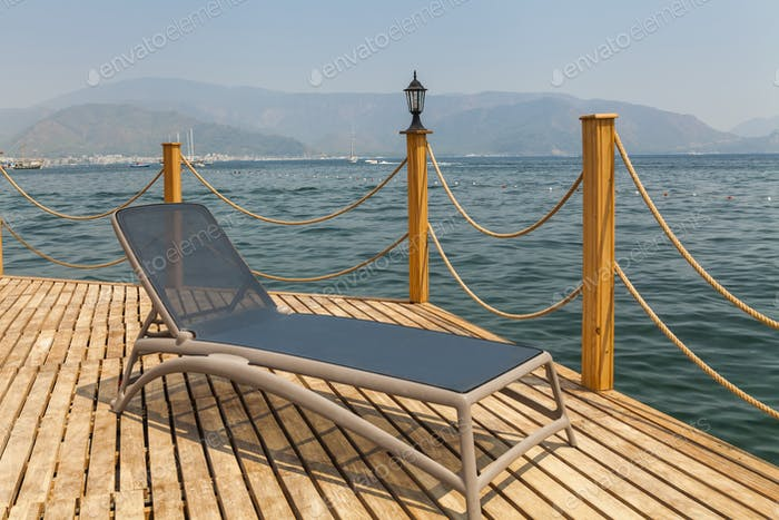 Sunbed on the wooden pier on the background of mountains and the sea port.