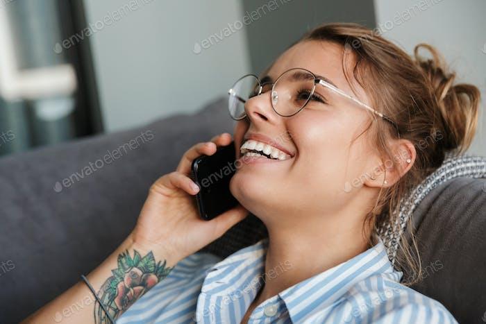 Sonriente joven empresaria hablando en el teléfono móvil