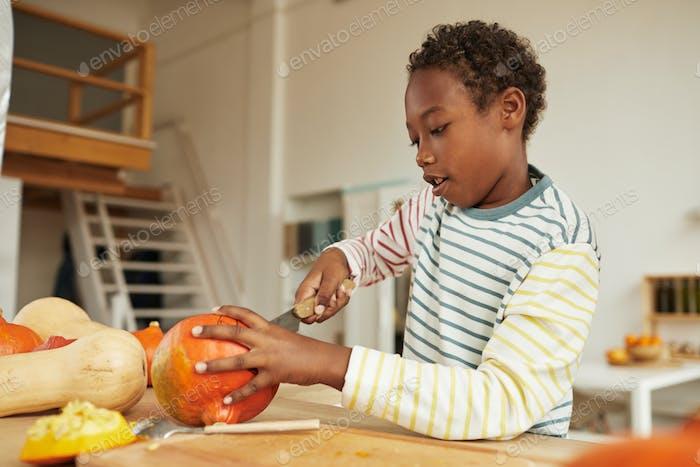 Boy Carving Pumpkin For Halloween