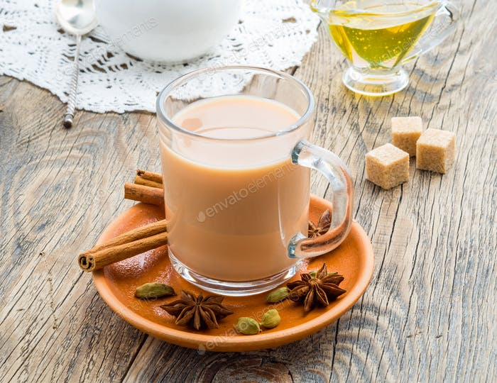 Masala Indian drink in the festival of Holi. Tea with milk and spices in a glass mug.