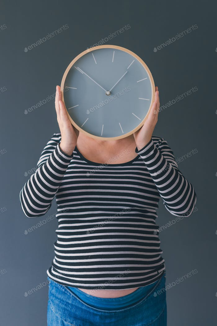 Pregnant female with vintage alarm clock