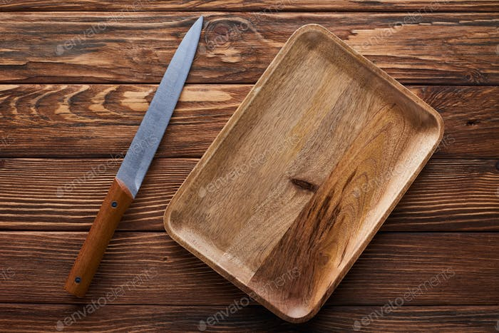 Top View of Empty Rectangular Dish Near Knife on Brown Wooden Surface