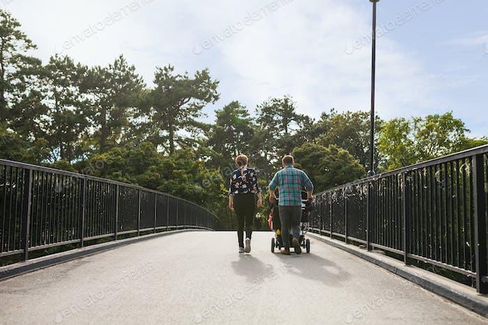 Couple pushing baby carriage on footbridge