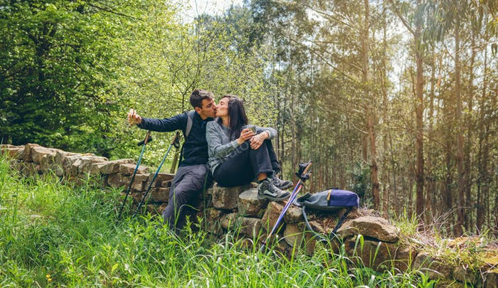 Couple kissing while making a break to do trekking