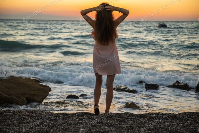 Young woman in summer dress on sunset background at sea.