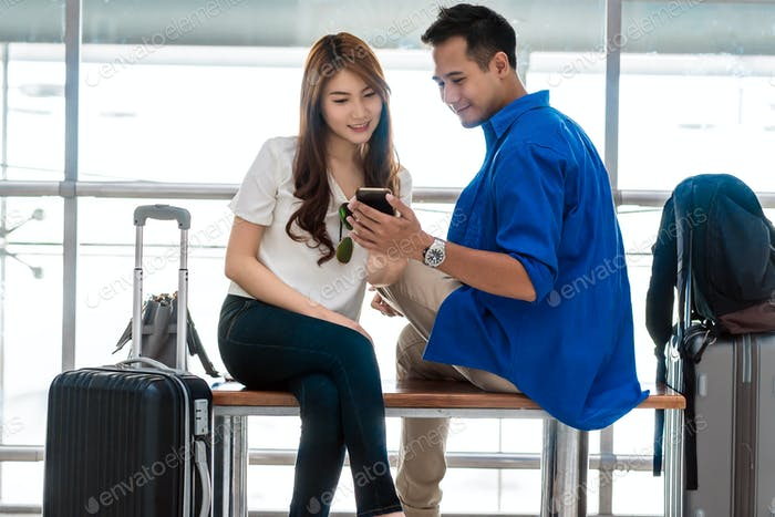 Asian couple traveler using smartphone and listening the song when waiting the airplane