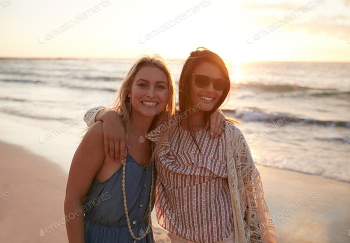 Beautiful young women standing together on the beach