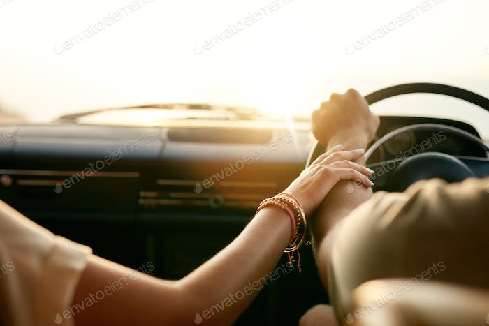 Young couple in their car holding hands