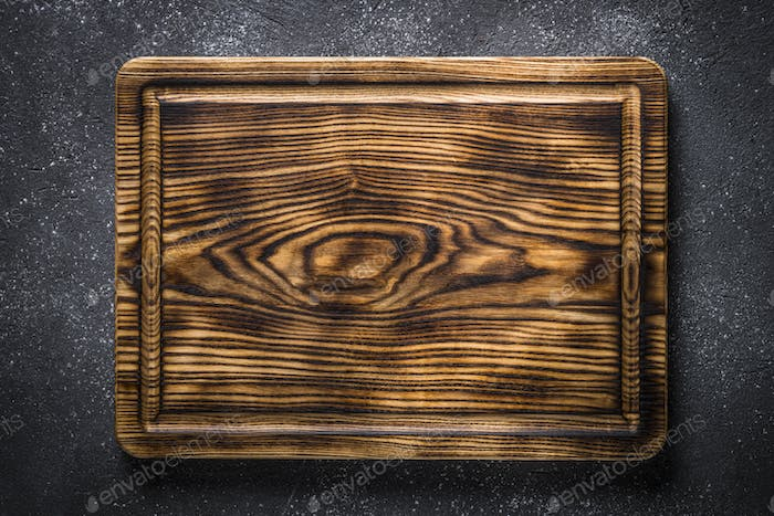 Wooden cutting board on black top view