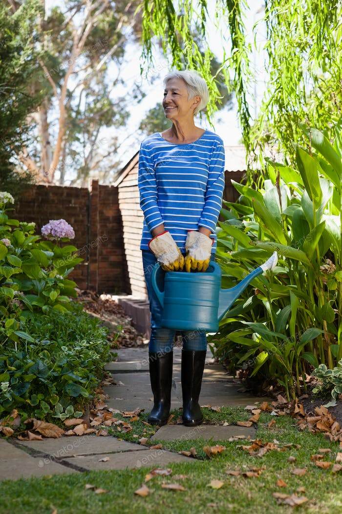 Full length of senior woman standing with watering can on walkway