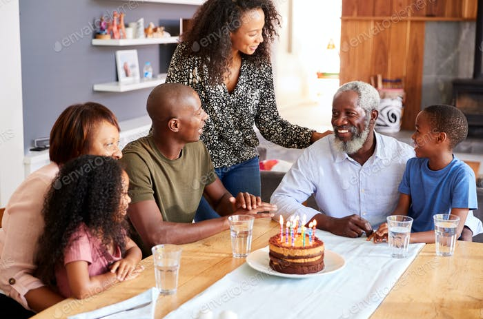 Multi-Generation Family Celebrating Grandfathers Birthday At Home With Cake And Candles