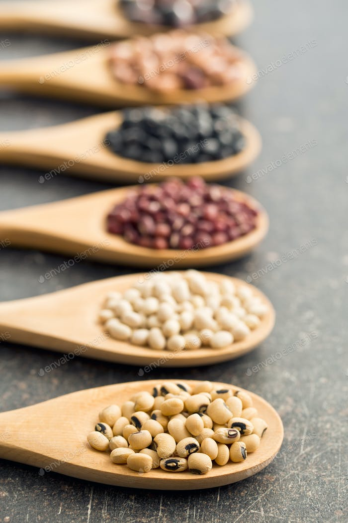 various legumes in wooden spoons