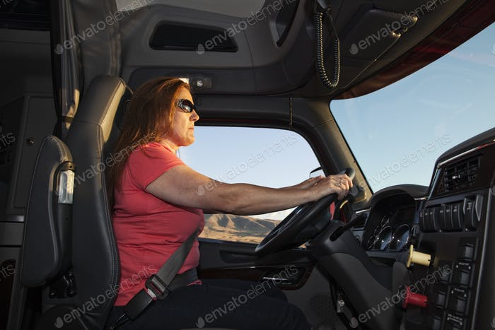 Interior cab view of a Caucasian woman driver driving her  commercial truck.