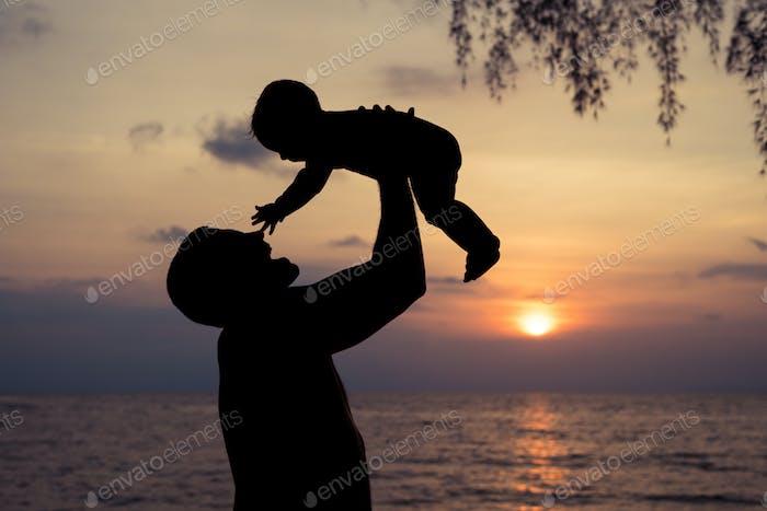 Vater und Baby Sohn spielen am Strand bei Sonnenuntergang Zeit.