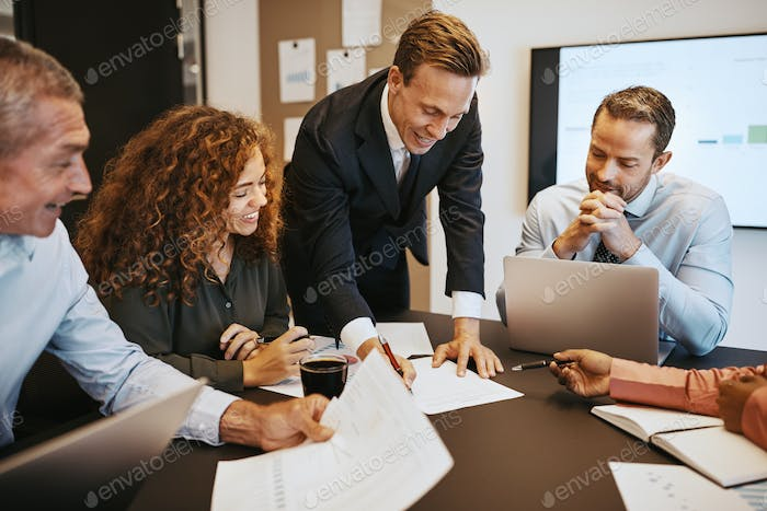 Smiling businesspeople going over paperwork together in an office boardroom