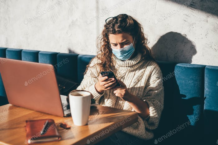 Woman with face mask using laptop and phone at the cafe.