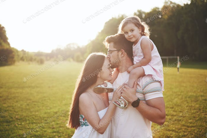 Happy family, father of mother and daughter of baby in the nature at sunset