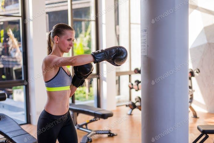 Attraktive weibliche Punching A Sack mit Boxhandschuhen On