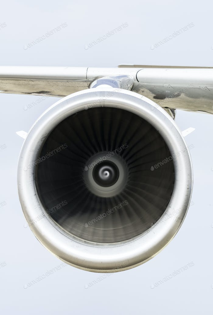 Jet engine on the airplane wing. Close-up frontal view of the jet engine and sky on the background.