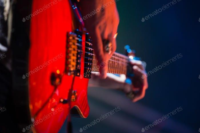 Nahaufnahme von Gitarrist spielt Gitarre auf der Bühne