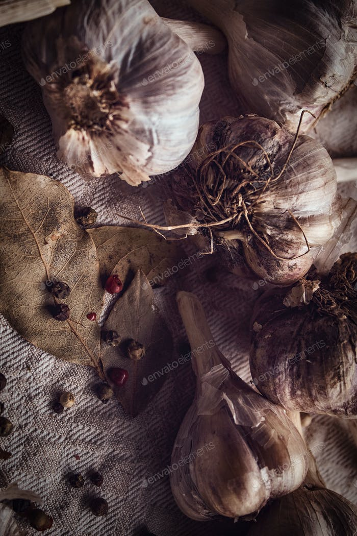 Photo of the fruits of black pepper, bay leaves, garlic scattered on a fabric sheet