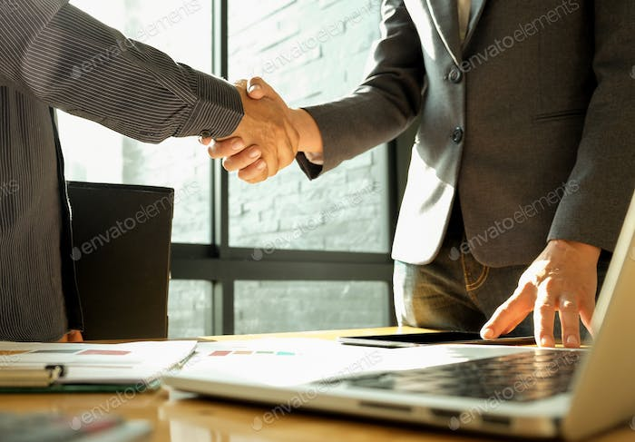 Two businessmen join hands after reaching a business agreement.