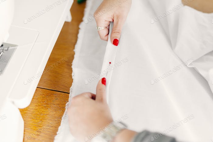 Designer's hands holding pinned up white fabric at table