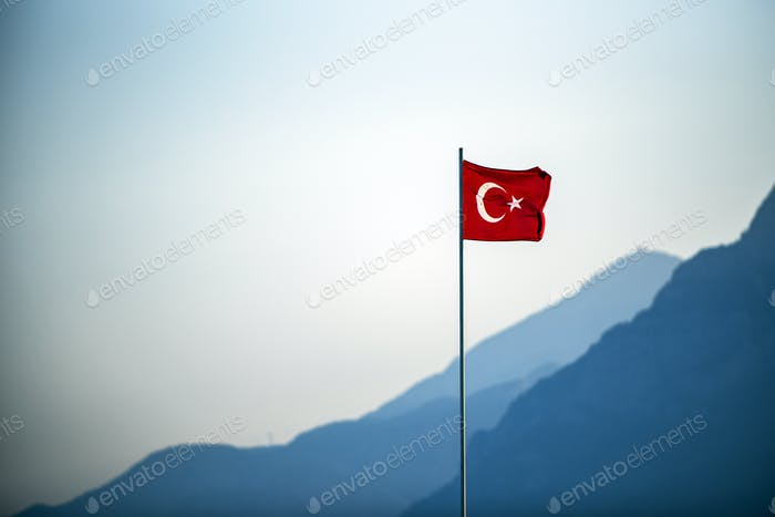 Turkish Flag waving on the wind with mountains in the background