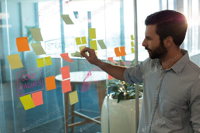 Businessman analyzing adhesive notes on glass