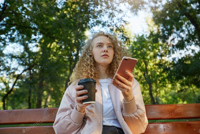A young beautiful girl blonde sits on a park bench, drinking coffee, looks on a companion, speaking