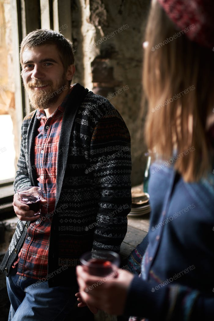 Happy yonug bearded man in casualwear holding glass of red homemade wine
