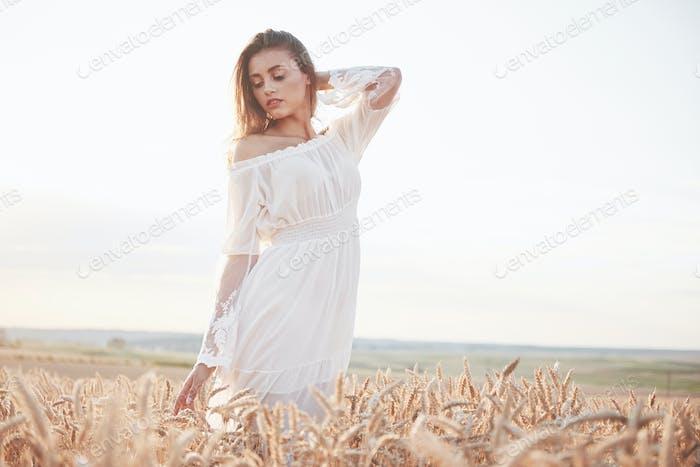 Porträt eines schönen Mädchens in einem weißen Kleid auf dem Gebiet der Weizen