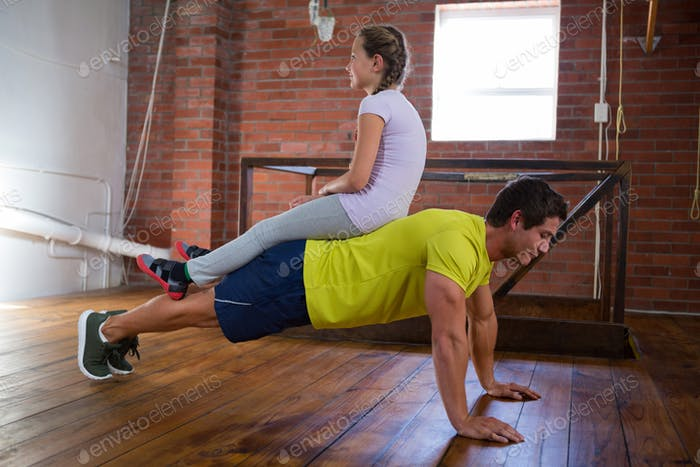 Trainer and teenage girl exercising in gym