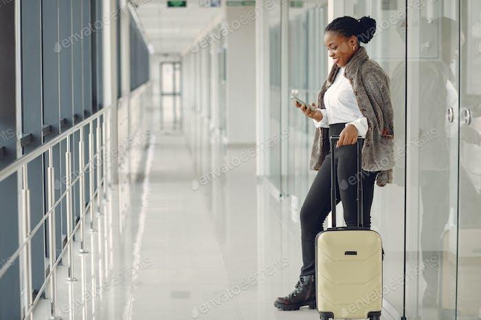 Schwarze Frau mit Koffer am Flughafen