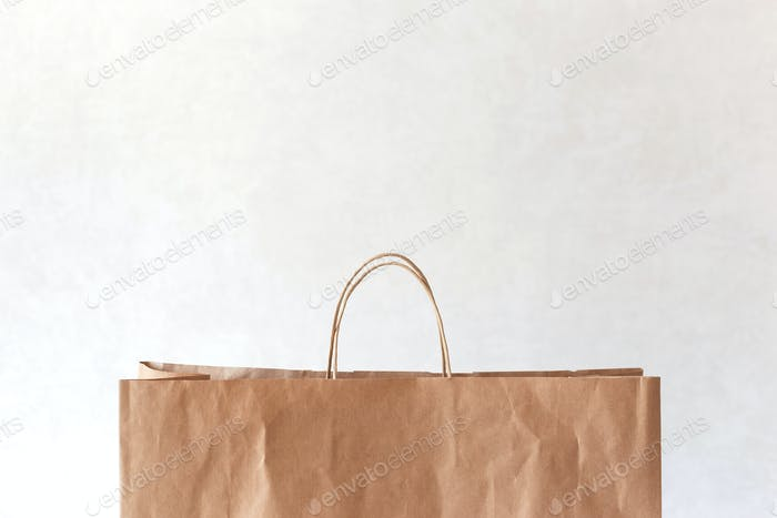 Blank brown paper bag with copy space on top on light background.
