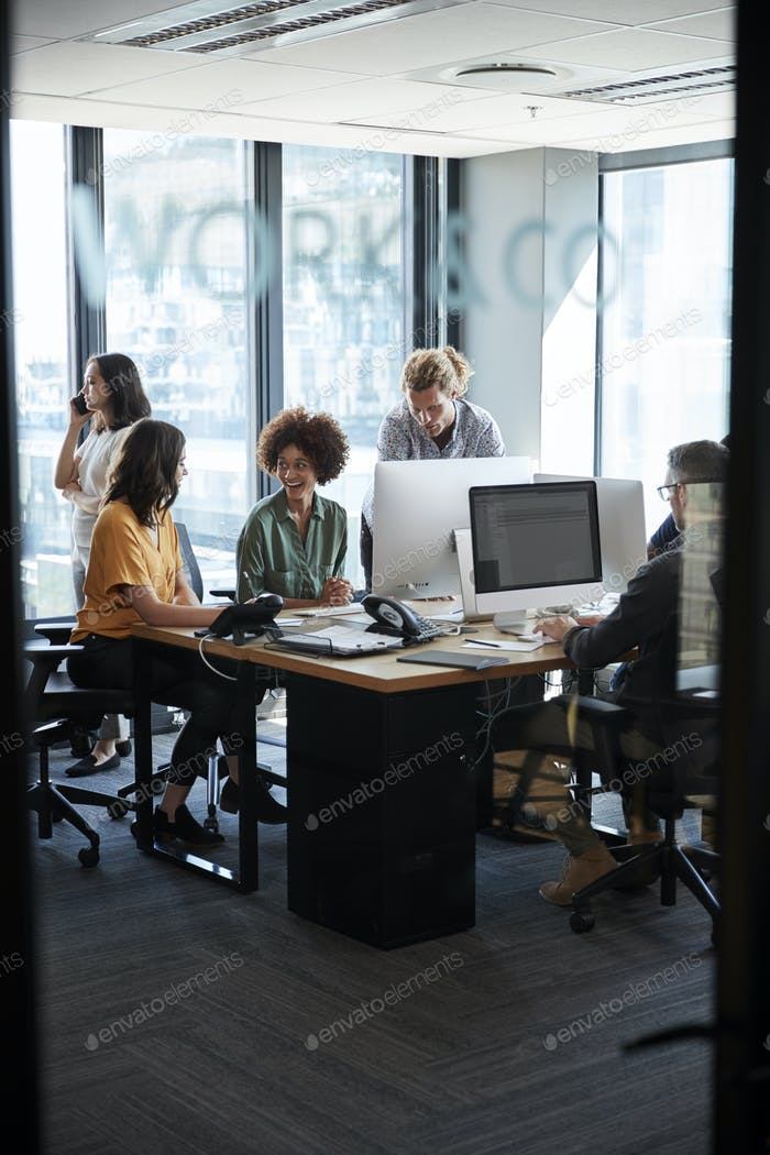 Creative colleagues in working in a casual office, seen through glass wall with text on it, vertical