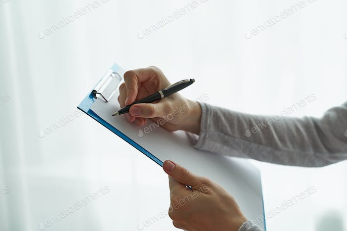 Woman holding clipboard, concept of office work or studying student side view closeup