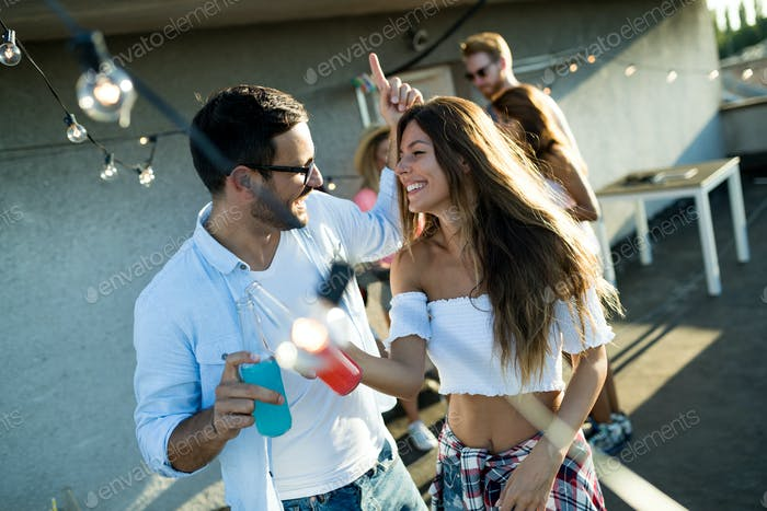 Happy young dancing couple having fun and enjoying party at summer