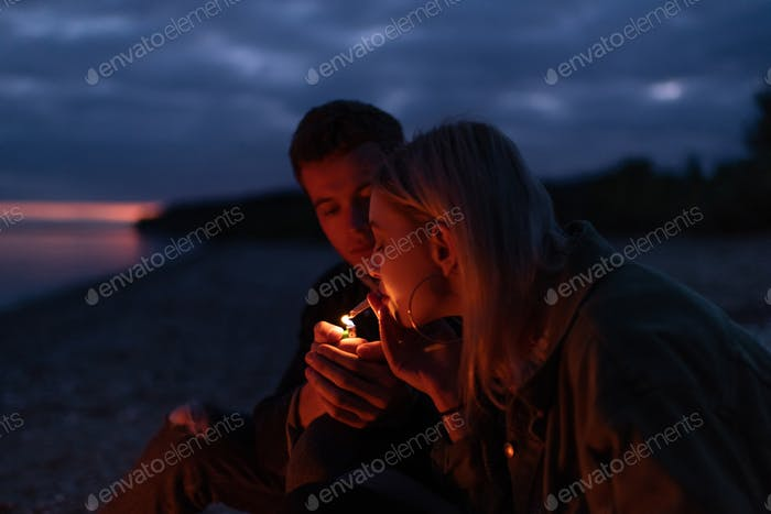 Hipsters relaxing with joint at autumn night