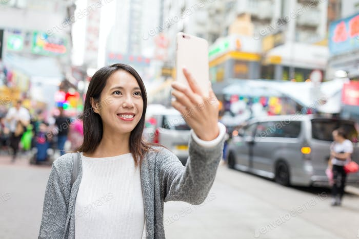 Woman having selfie with cellphone in city of Hong Kong