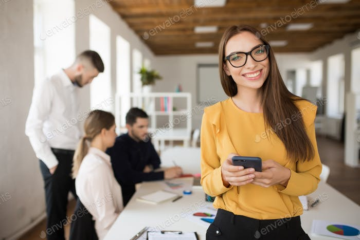 Young business woman in eyeglasses happily looking in camera whi