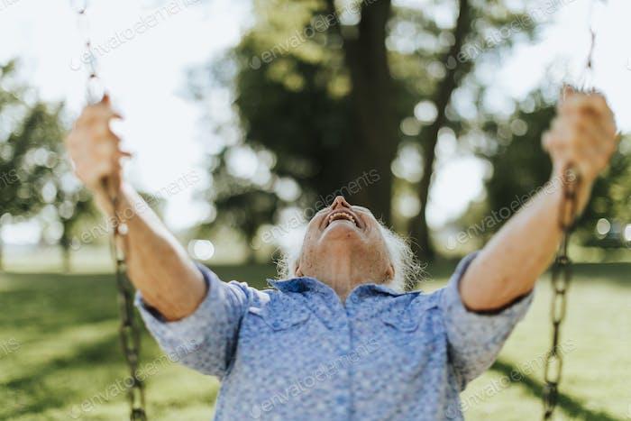 Fröhliche Seniorin auf einer Schaukel auf einem Spielplatz