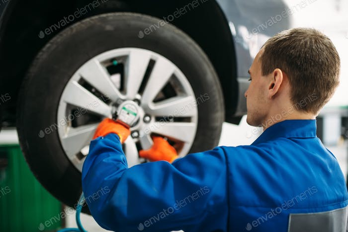 Mechanic unscrews the wheel, tire service