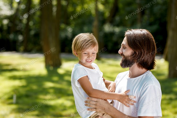 Man and boy in white t shirts. Man with dark hair is holding a boy with blonde hair in his arms boy