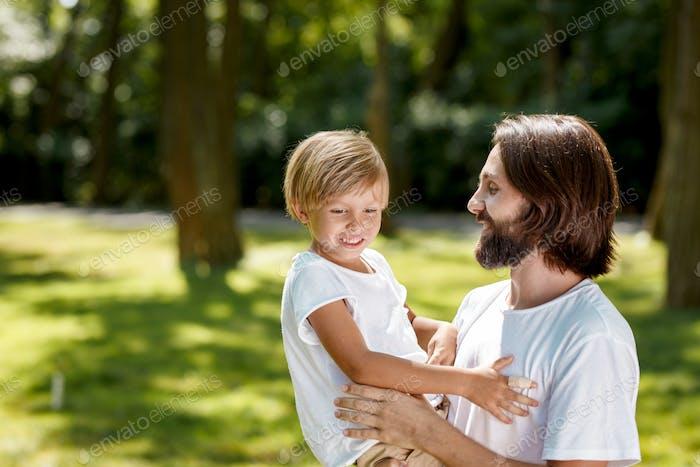 Mann und Junge in weißen T-Shirts. Mann mit dunklen Haaren hält einen Jungen mit blonden Haaren in den Armen Junge