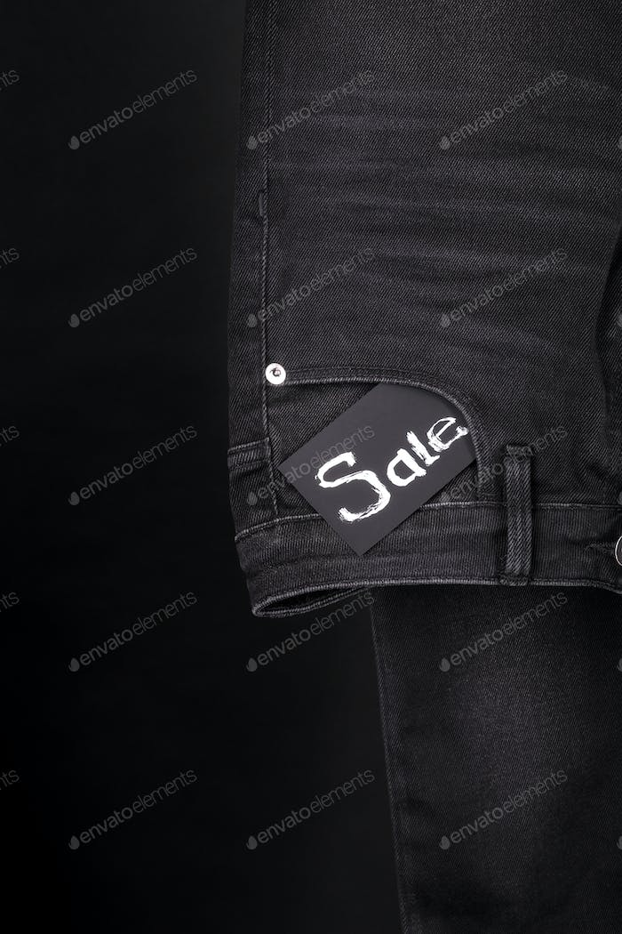sale.Friday. Close up of black jeans with sign  on  background.