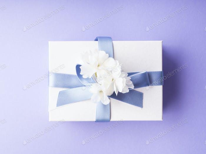 Weiße Geschenkbox mit blauem Band und Dekorblumen auf lila verpackt